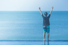 Frau, die auf Rand des Swimmingpools mit den angehobenen Händen Unkosten, sie Meerblickansicht betrachtend steht stockfotos