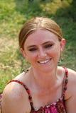 Frau, die auf Rasen lächelt Lizenzfreie Stockbilder