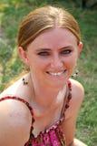 Frau, die auf Rasen lächelt Lizenzfreie Stockfotos