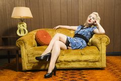Frau, die auf Retro- Couch sitzt. Lizenzfreie Stockfotos