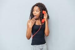 Frau, die auf Retro- Telefonrohr spricht und weg schaut Stockfotografie