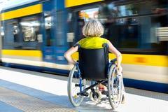 Frau, die auf Rollstuhl auf einer Plattform sitzt stockfotografie