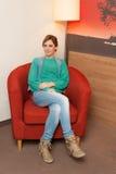 Frau, die auf rotem Stuhl sitzt Stockfotografie