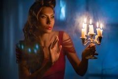 Frau, die auf roten Kerzen in der fabelhaften Nacht schaut Stockfoto