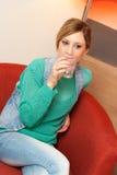 Frau, die auf roter Stuhl-Trinkwasser sitzt Stockfotos