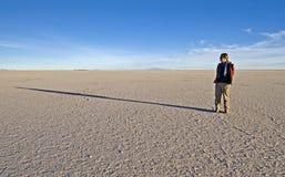 Frau, die auf Salz-Ebenen steht lizenzfreie stockbilder
