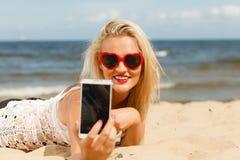 Frau, die auf sandigem Strand unter Verwendung des Handys liegt stockbild