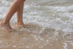 Frau, die auf Sandstrand geht Stockfoto