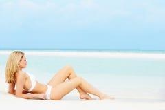 Frau, die auf schönem Strandurlaub ein Sonnenbad nimmt Stockfoto