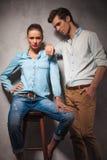 Frau, die auf Schemel sitzt, während Freund auf ihrer Schulter sich lehnt Stockbilder
