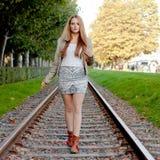 Frau, die auf Schienenstrang geht Stockfotografie