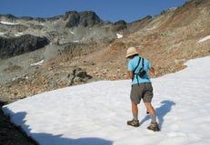 Frau, die auf Schnee am Sommer wandert Stockbild