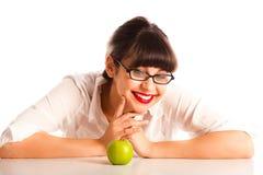 Frau, die auf Schreibtisch in den Gläsern mit Apfel stillsteht Lizenzfreie Stockfotos