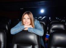 Frau, die auf Seat am Kino sich lehnt Lizenzfreie Stockfotos