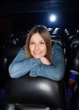 Frau, die auf Seat am Kino-Theater sich lehnt Stockfotos