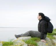 Frau, die auf Seeklippe sitzt Stockfotos