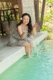 Frau, die auf Seite des privaten Swimmingpools sich entspannt stockbilder