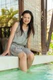 Frau, die auf Seite des privaten Swimmingpools sich entspannt stockfoto