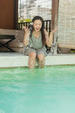 Frau, die auf Seite des privaten Swimmingpools sich entspannt stockfotografie