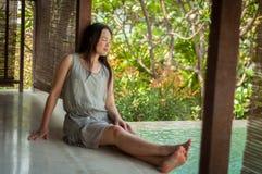 Frau, die auf Seite des privaten Swimmingpools sich entspannt stockbild