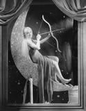Frau, die auf sichelförmigem Mond mit Pfeil und Bogen sitzt Lizenzfreie Stockfotos
