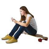 Frau, die auf Skateboard sitzt und intelligentes Telefon verwendet Stockbild