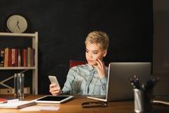 Frau, die auf Smartphone beim Büro zu Hause bearbeiten simst Stockbild