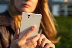 Frau, die auf Smartphone schaut Lizenzfreies Stockfoto
