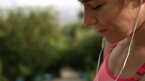 Frau, die auf Smartphone schaut und Musik hört stock footage