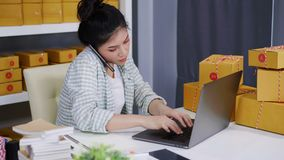 Frau, die auf Smartphone- und Gebrauchscomputerlaptop mit dem Verkauf des Produktes online vom Innenministerium spricht stock footage