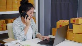 Frau, die auf Smartphone- und Gebrauchscomputerlaptop mit dem Verkauf des Produktes online vom Innenministerium spricht stock video footage