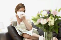 Frau, die auf Sofa Blowing Nose sitzt Lizenzfreie Stockbilder