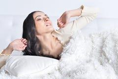Frau, die auf Sofa At Home aufwacht Lizenzfreies Stockbild