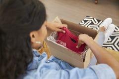 Frau, die auf Sofa At Home Opening Online-Kleidungs-Kauf sitzt Stockfotografie