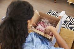 Frau, die auf Sofa At Home Opening Online-Kleidungs-Kauf sitzt Lizenzfreies Stockbild