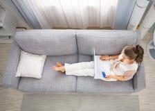 Frau, die auf Sofa legt und das on-line-Einkaufen macht Stockbild
