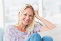 Frau, die auf Sofa In Living Room sich entspannt Stockfotos