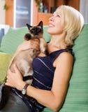 Frau, die auf Sofa mit ihrer Katze sitzt Lizenzfreies Stockbild