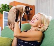 Frau, die auf Sofa mit ihrer Katze sitzt Lizenzfreie Stockbilder