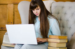 Frau, die auf Sofa mit Laptop sitzt stockbild