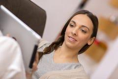 Frau, die auf Sofa mit Tabletten-PC sitzt Lizenzfreies Stockfoto