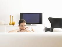 Frau, die auf Sofa In Modern Living Room sitzt Stockfoto