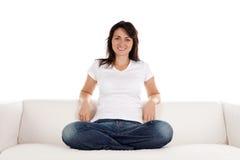 Frau, die auf Sofa sich entspannt Stockbilder