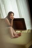 Frau, die auf Sofa sich entspannt stockfoto