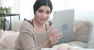 Frau, die auf Sofa unter Verwendung der digitalen Tablette für Videoschwätzchen liegt stock footage