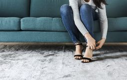 Frau, die auf Sofa zu tragenden hohen Absätzen sitzt stockbilder