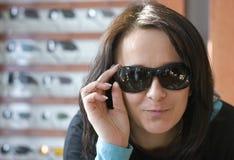 Frau, die auf Sonnenbrillen versucht Lizenzfreie Stockfotos