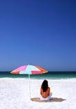 Frau, die auf spanischem Strand unter Sonneregenschirm sitzt. Blaues Meer und Himmel des weißen Sandes. Lizenzfreie Stockfotos