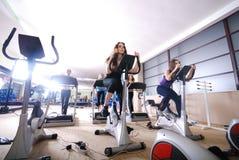 Frau, die auf spinnendem Fahrrad an der Gymnastik ausarbeitet Stockfoto