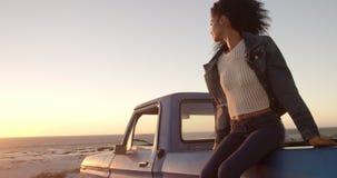 Frau, die auf Stamm des Kleintransporters am Strand 4k sitzt stock footage